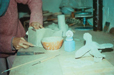 photo showing a potter at work on a ceramic piece